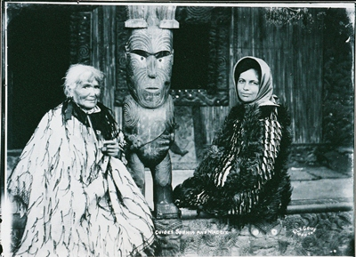 Guide Sophia Hinerangi and Guide Maggie Papakura sitting on the porch of Nuku Te Apiapi, Whakarewarewa, date unknown, photograph by Edward Le Grice (1881–1959). Rotorua Museum (GP-162 )